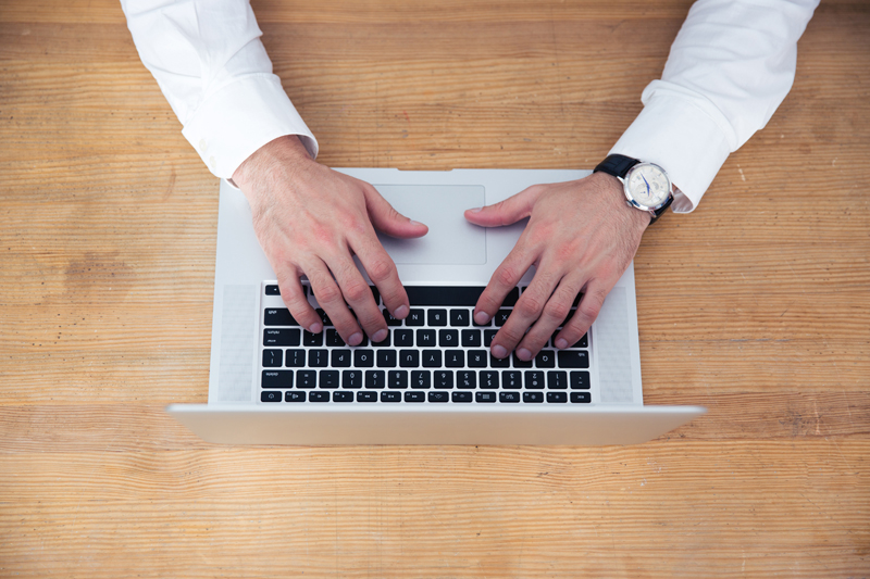 Closeup image of a businessman hands using laptop on wooden table